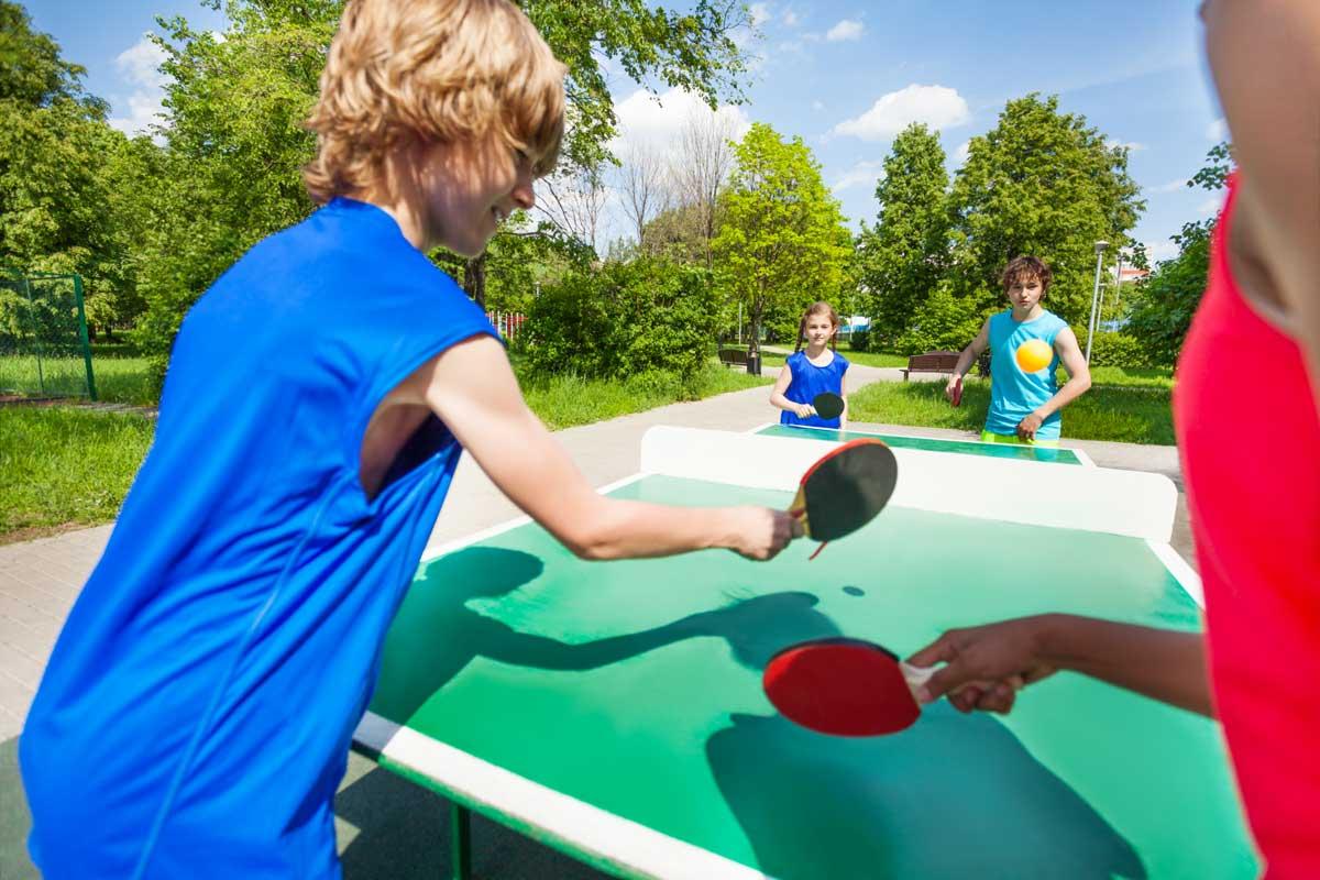 Kinder spielen Tischtennis im Garten